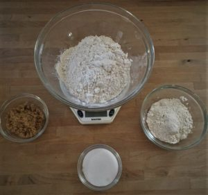 Kitchen scale, bowls of flour, sugar, and brown sugar