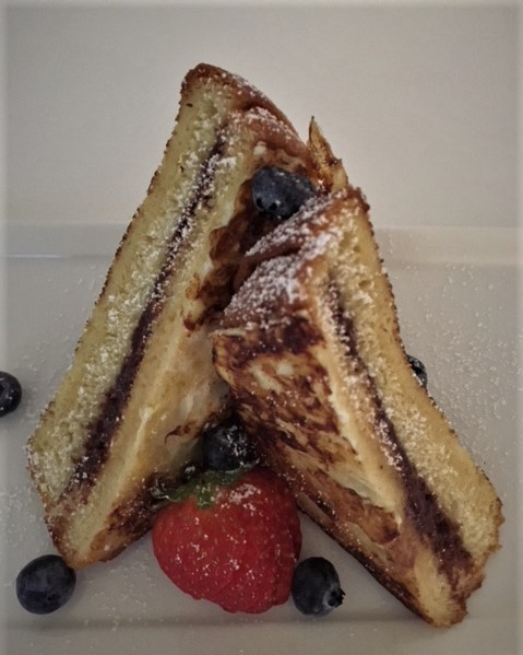 French Toast triangles on a plate with fresh berries
