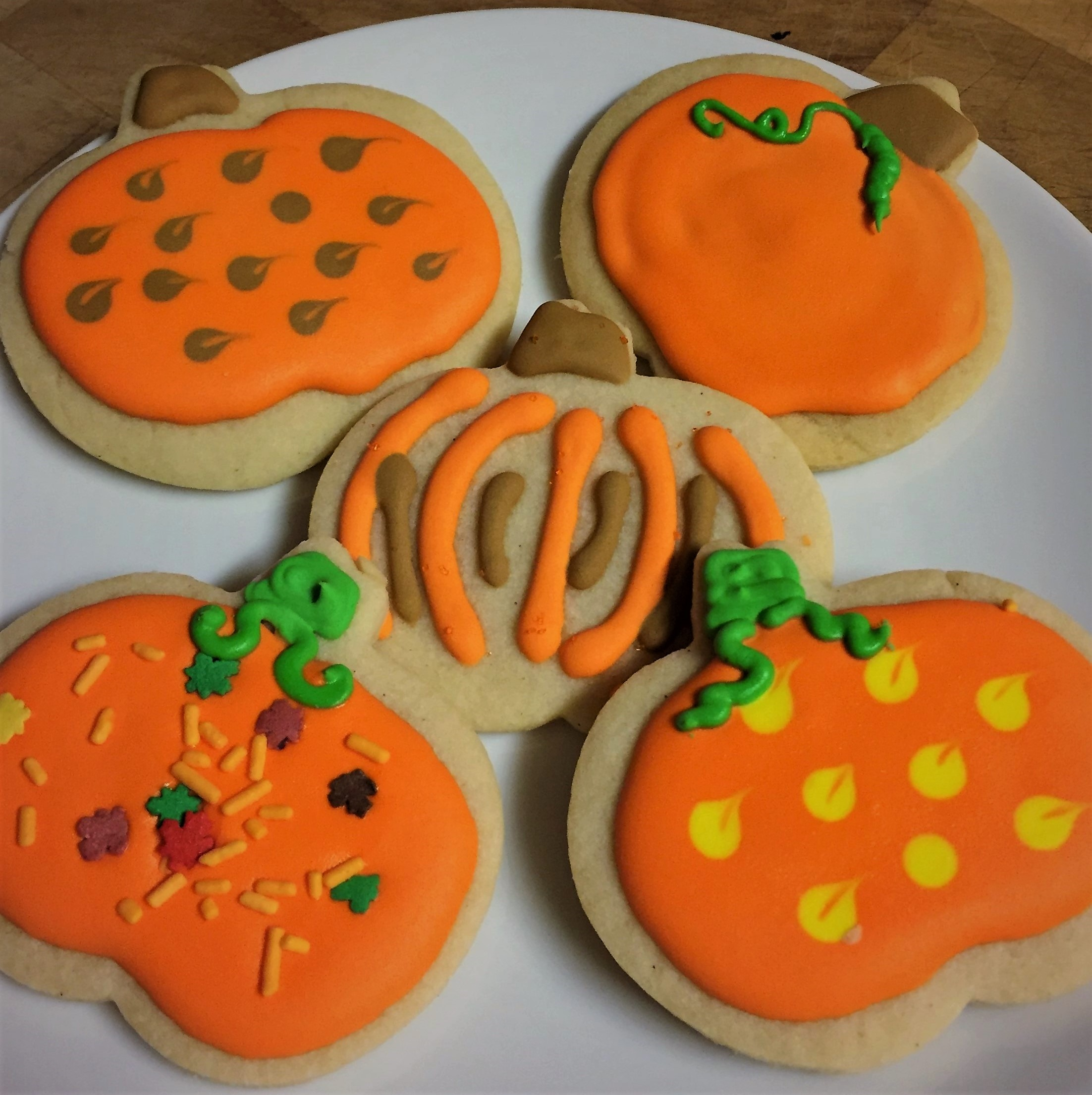 pumpkin cookie cutouts decorated in orange, brown, and yellow