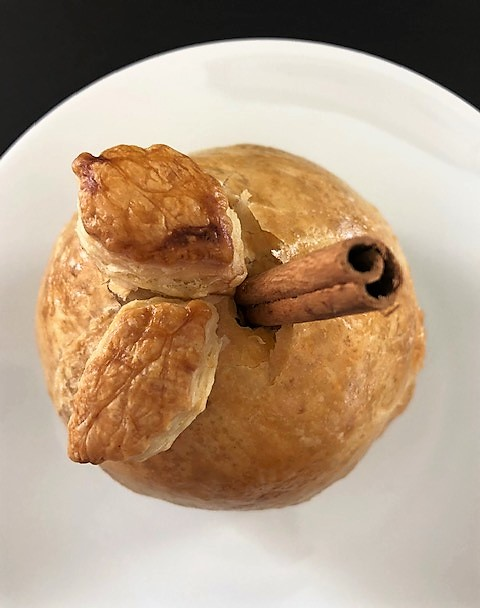 Baked apple dumpling with decorative leaves and cinnamon stick