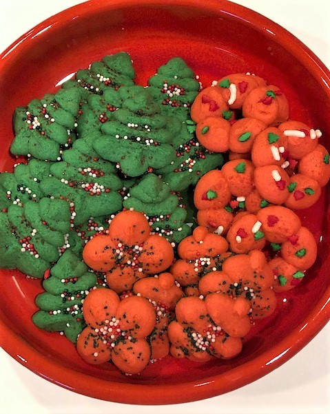 Green and red spritz cookies on a decorated platter