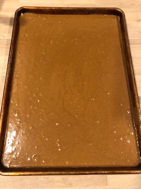 gingerbread cake batter in a sheet pan ready to bake