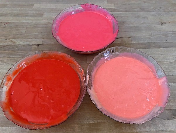 three bowls of valentine colored cake batter