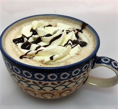 Hot chocolatte in a cup with whipped cream and chocolate sauce