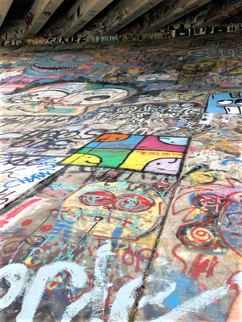 artist painting under bridge inman park