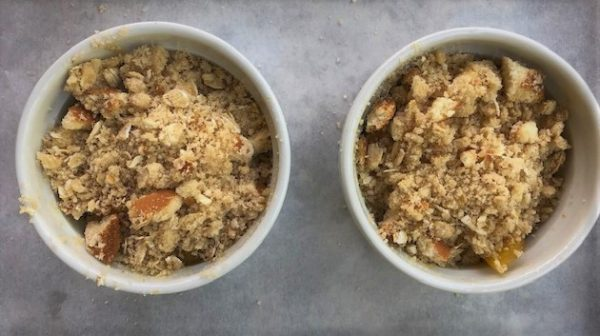 adding crumb topping to peach cobbler
