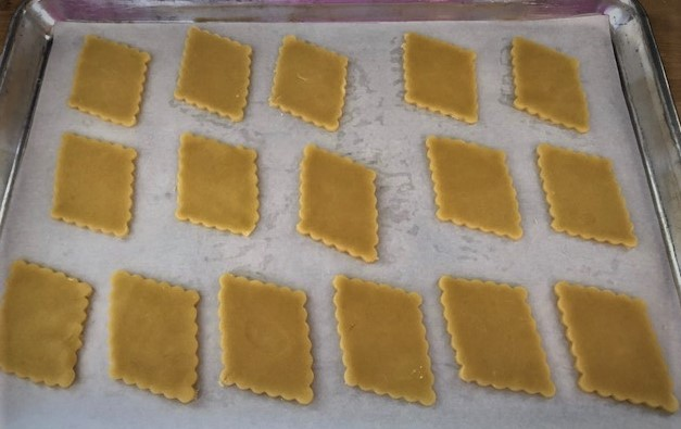 diamond cut out pastries on baking sheet