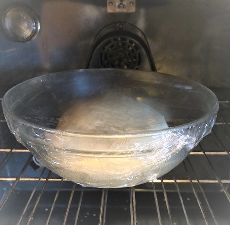 placing dough into oven to rise