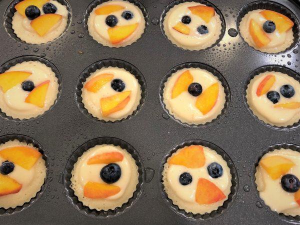 peach blueberry cakes in mini tart pan ready to bake