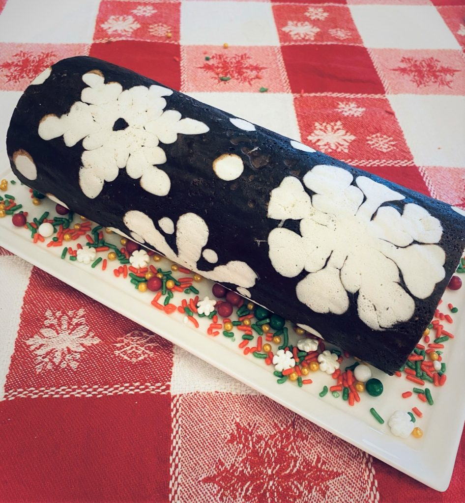 chocolate snowflake cake roll on a plate with srpinkles