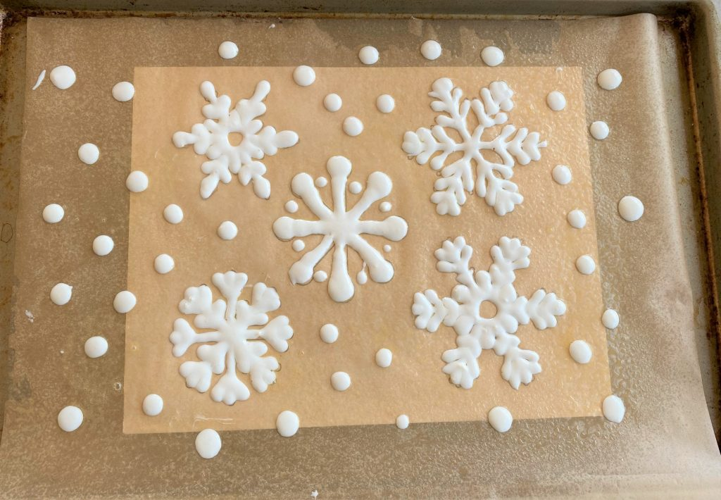 snowflakes piped on parchment paper