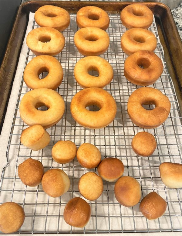 Fried donuts on a sheet pan ready to glaze