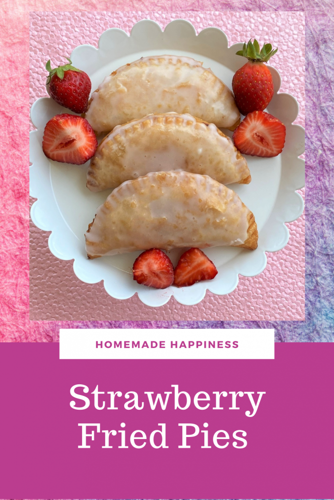 strawberry fried pies on a platter with fresh strawberries