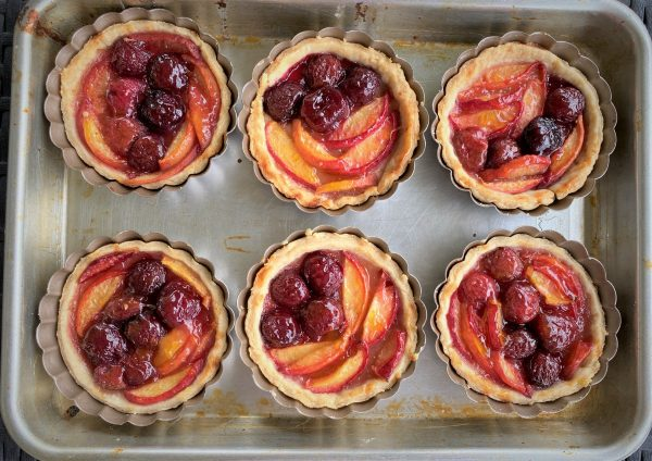 baked cherry and peach pies on a sheet pan