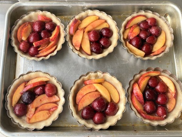 assembling peach and cherry pies in pie shells
