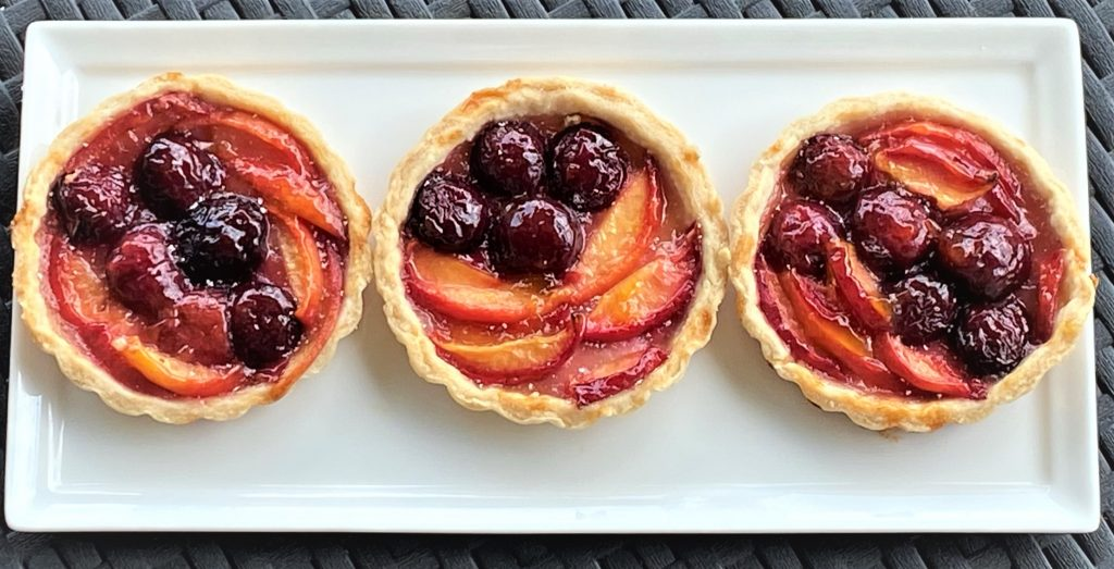 trio of peach and cherry pies on a platter