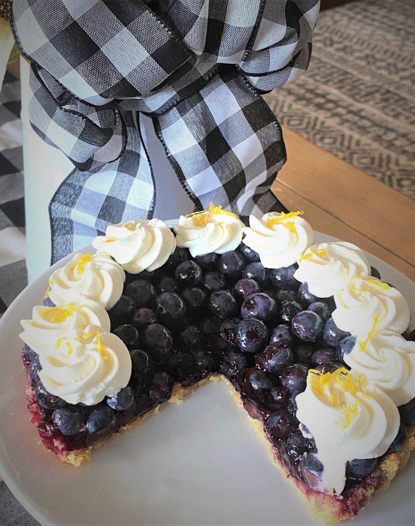 lemon cookie blueberry tart sliced on a plate