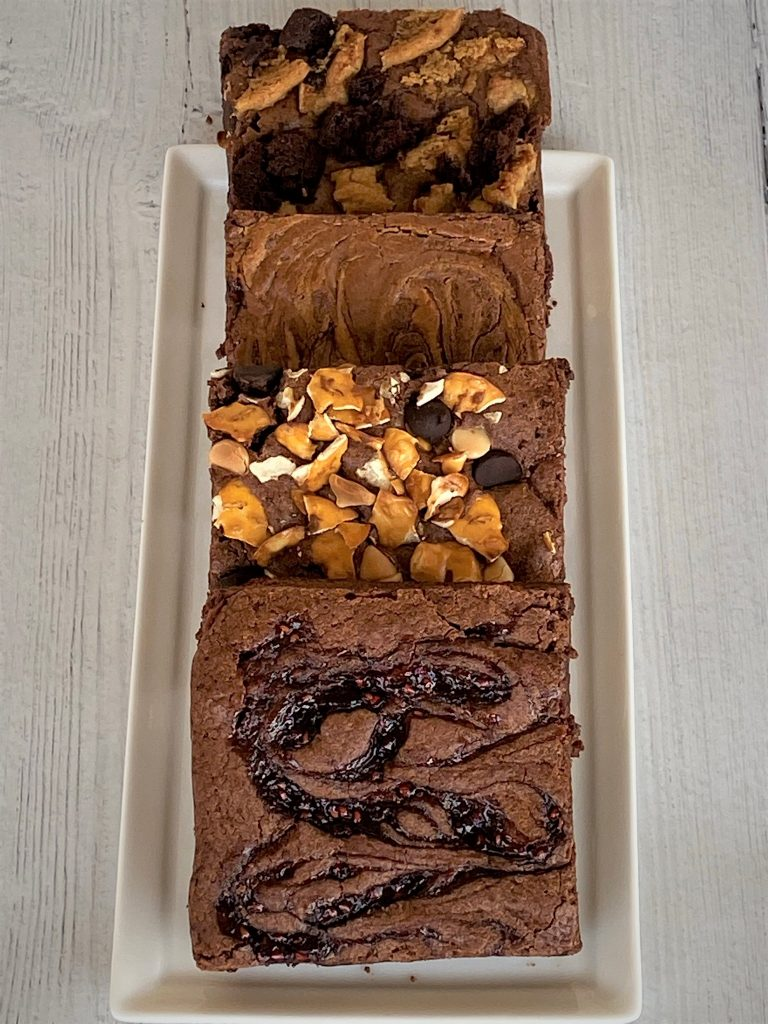 sliced 4 brownies with various toppings on a plate