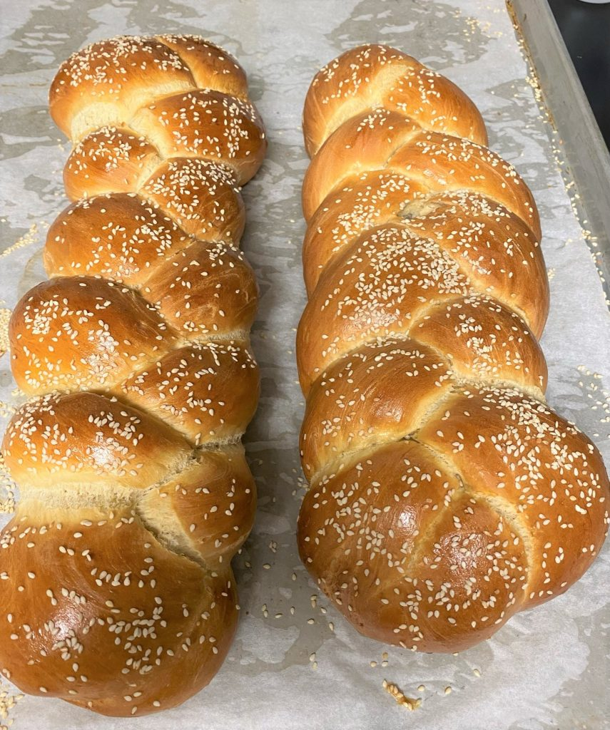 two challah breads on a baking sheet